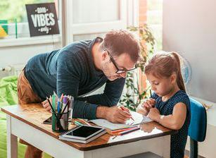 Vater kontrolliert Hausaufgaben und Kind