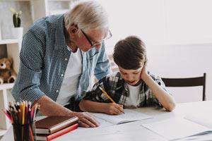 älterer Mann hilft Kind bei Hausaufgaben