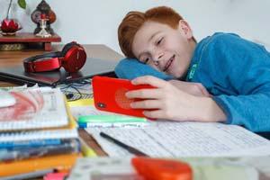 Junge spielt am Handy während der Hausaufgaben