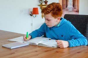 Junge macht die Hausaufgaben an einem aufgeräumten Arbeitsplatz
